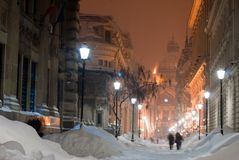 Lighted city alley in winter. Evening lights on an snowy european city alley stock image