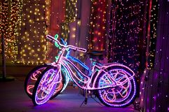 Lighted funky bicycles. Glowing psychedelic bikes with multicolored Christmas lights Stock Photography