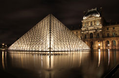 Lighted glass pyramid and Louvre Palace Royalty Free Stock Image