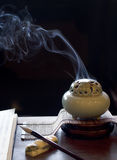 Lighted incense burner is placed on the table Royalty Free Stock Photos