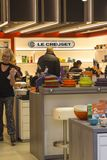 The lighted interior of the Le Creuset shop at Ireland`s prestigious Kildare Village retail outlet. With a smiling shop assistant about her businessn royalty free stock photography