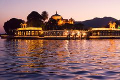 Lighted island palace on lake in Udaipur. Jag mandir lake palace on the artifical lake pichola shot at night with the lights switched on. The beautiful golden Stock Photo