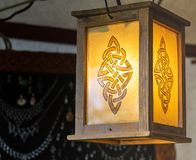 Lighted lantern with an abstract pattern resembling a rune, wooden frame with yellow glass stock photos