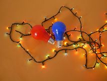 Lighted lanterns for illumination, bulbs red and blue on a bright yellow background, top view. The concept of seasonal decoration home holiday stock photo
