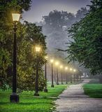 Lighted Park Path in the Morning. Empty park footpath is lighted in the early morning in Regents park, London Royalty Free Stock Photos