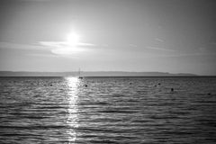 Lighted Path. Grayscale photo of a boat in the path of light Royalty Free Stock Photos
