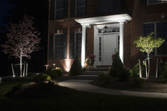 Lighted path to door. A front walk is illuminated to the front door of a house.  Accent lights decorate the front gardens of the estate Stock Photography