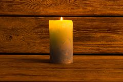 Lighted pillar candle. On wooden background. Home decorating element. Cozy atmosphere and warm light Royalty Free Stock Images