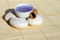 Lighted purple candle on bamboo Royalty Free Stock Image