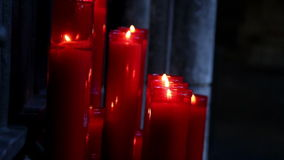 Lighted red candles in a dim-lighted place in church stock video footage