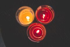 Lighted Red Wax Candle on Clear Drinking Glass Royalty Free Stock Photos