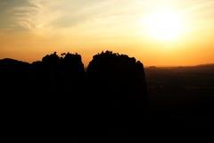 Lighted rocks and hills bellow sunset sun on  horizon. Dark silhouettes. Royalty Free Stock Photos