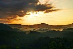Lighted rocks and hills bellow sunset sun on  horizon. Dark silhouettes. Stock Image