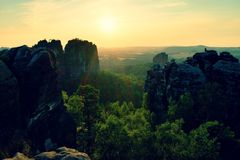 lighted rocks and hills bellow sunset sun on  horizon. Dark silhouettes. Stock Photo