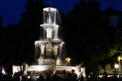 Lighted running fountain under dark nighttime sky. Lighted running three tiered fountain surrounded by flowers under dark nighttime sky Stock Photos