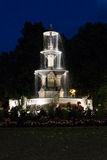 Lighted running fountain under dark nighttime sky. Lighted running three tiered fountain surrounded by flowers under dark nighttime sky Royalty Free Stock Photography