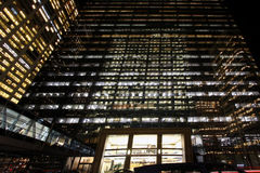 Lighted skyscraper at night. Exterior of modern skyscraper illuminated at night with entrance in foreground Royalty Free Stock Photos