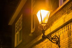 Lighted street lantern on the wall of a house at night, city scenery in the evening, vintage decoration. A lighted street lantern on the wall of a house at night stock photos