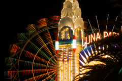 Lighted tower with colorful Ferris wheel blur at night Stock Image