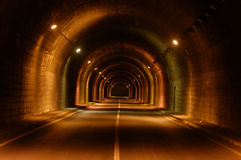 Lighted tunnel. A view of a lighted roadway passing through a dark tunnel Stock Photography