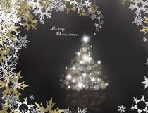 Lighted up Christmas tree with many lens flares. On grey background and Merry Christmas text Royalty Free Stock Image