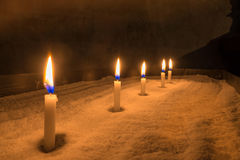 Lighted votive candles. Five lighted, small, white votive candles on a sand-filled metal table in a dark room Stock Image