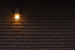 Lighted wall. A black wall with a brick pattern lighted by a retro wall lamp Stock Photos