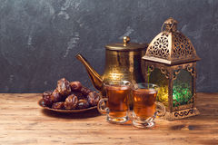 Lightened lantern, tea cups and dates on wooden table over blackboard background. Ramadan kareem holiday celebration. Concept royalty free stock image