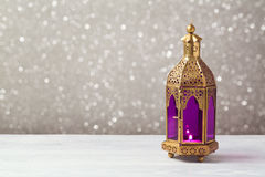 Lightened lantern on wooden table over bokeh background. Ramadan kareem holiday celebration. Concept Stock Images