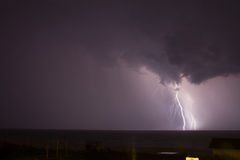 Lightening. In the distance on the ocean royalty free stock photos