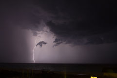 Lightening. In the distance on the ocean royalty free stock image