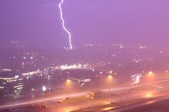 Lightening and heavy rain. City of Montreal is in a heavy rain. Lightening is breaking the night sky presenting the power of nature. The sky is purple and empty Stock Images