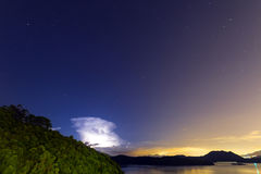 Lightening at night in a clear sky with huge amount of stars. In Sai Kung, Hong Kong royalty free stock image
