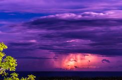 Lightening Storm over the ocean at night. Lightning bolts striking. Pink, purple and blue skies stock photography