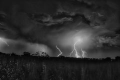 Lightening strikes on horizon. Black and white landscape of multiple cloud to ground lightening strikes in countryside Royalty Free Stock Images
