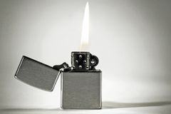 Lighter. A stainless steel lighter burning on a white background Stock Images