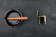 Lighter and black ashtray with cigar Royalty Free Stock Photo