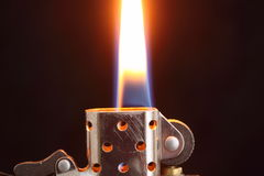 Lighter flame. A stainless steel lighter with its flame showing Royalty Free Stock Photography