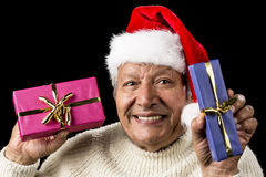 Lighthearted, Smiling Old Man Offering Two Gifts. Gently smiling male pensioner proffering a blue and a pink wrapped present. Each with golden bow. Red Santa Royalty Free Stock Images