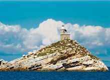 Lighthous on a white rock in Elba. Lighthouse built in Napoleon era on a white cliff. The rock surrounded by blue sea. Surrounded by white clouds stock photography