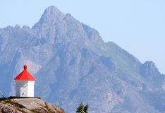 Lighthouse. Small red and white lighthouse with a mountain in the background, Lofoten Islands, Norway Royalty Free Stock Photos