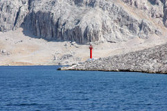 Lighthouse. Red see light on island with mountain background Royalty Free Stock Image