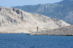 Lighthouse. Red see light on island with mountain background Royalty Free Stock Photos