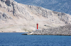 Lighthouse. Red see light on island with mountain background Stock Photos