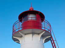 Lighthouse. Top of small red/white lighthouse on blue sky Stock Photos