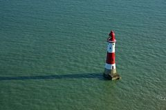 Lighthouse. Red and white lighthouse in sea Royalty Free Stock Image