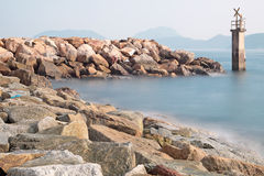 Lighthouse. On a Rocky Breakwall: A small  warns of a rough shoreline Royalty Free Stock Images