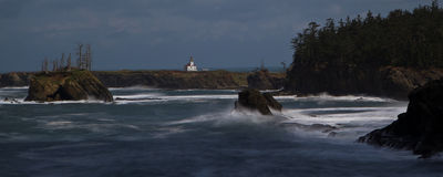 Lighthouse. Lone lighthouse in background with waves and rough sea crashing against islands and shoreline Stock Image