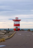Lighthouse. Small red white striped lighthouse on the end of the beach promenade, Scheveningen / Hague, Netherlands stock photography