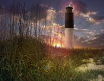 Lighthouse. In spectacular sunset, blades of grass in the foreground Stock Image